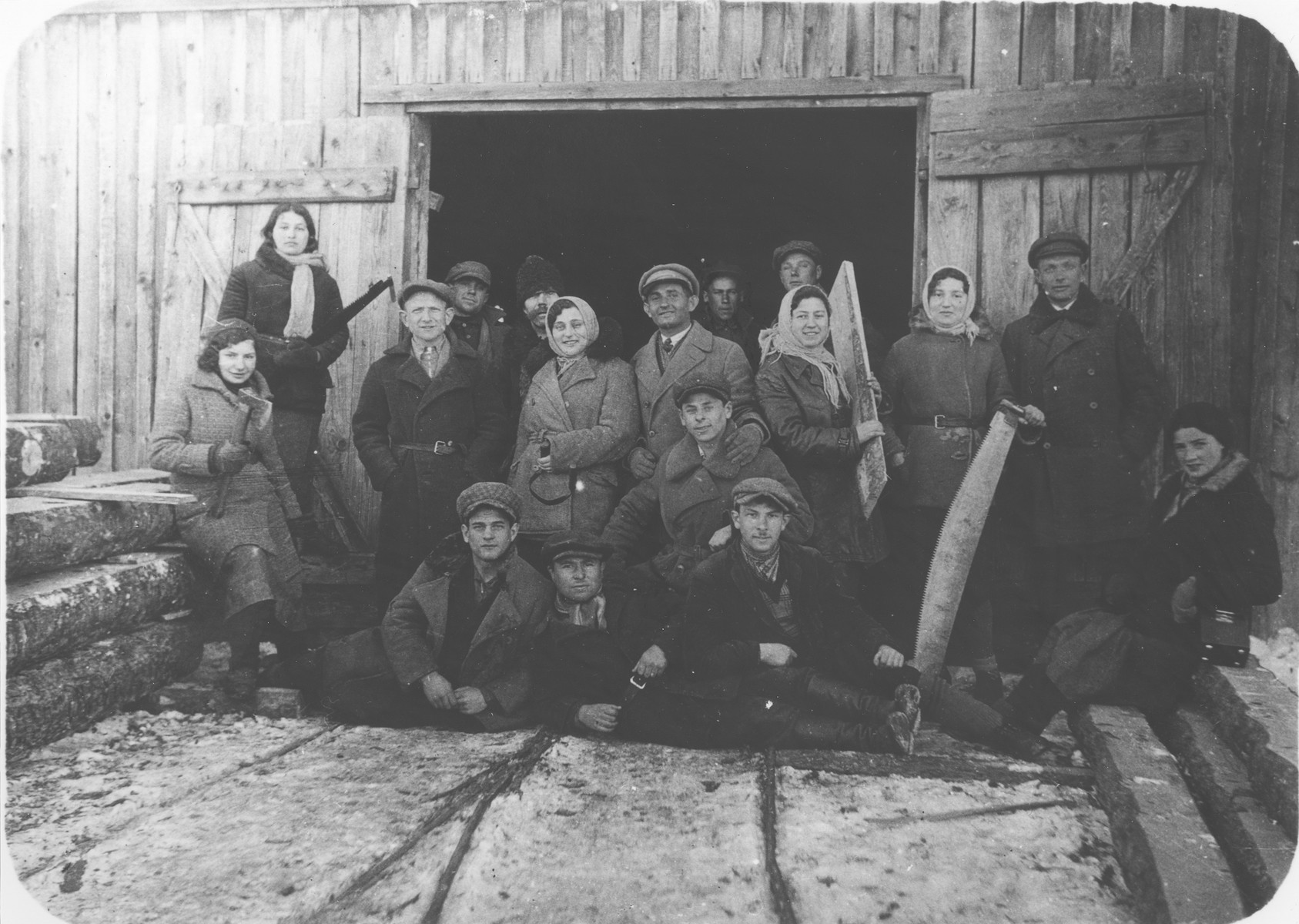 A group of young Zionists pose in front of a shed at a lumberyard in Bedzin prior to the departure of one of their members for Palestine.  Pictured holding the plank of wood is Bela Grajcer.