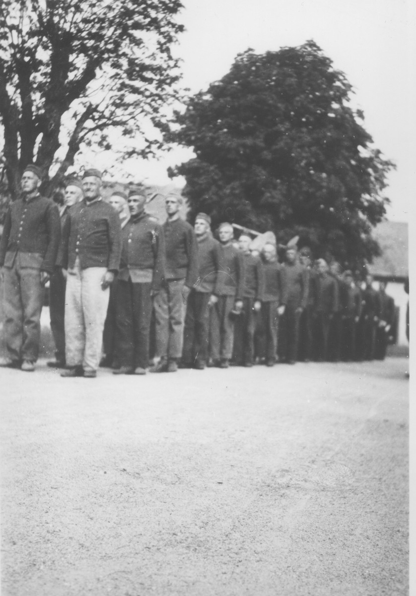 A group of Czech political prisoners interned in Theresienstadt stand in formation as they reenter the camp after a day at forced labor.  Among those pictured is Oskar Bartolsic.