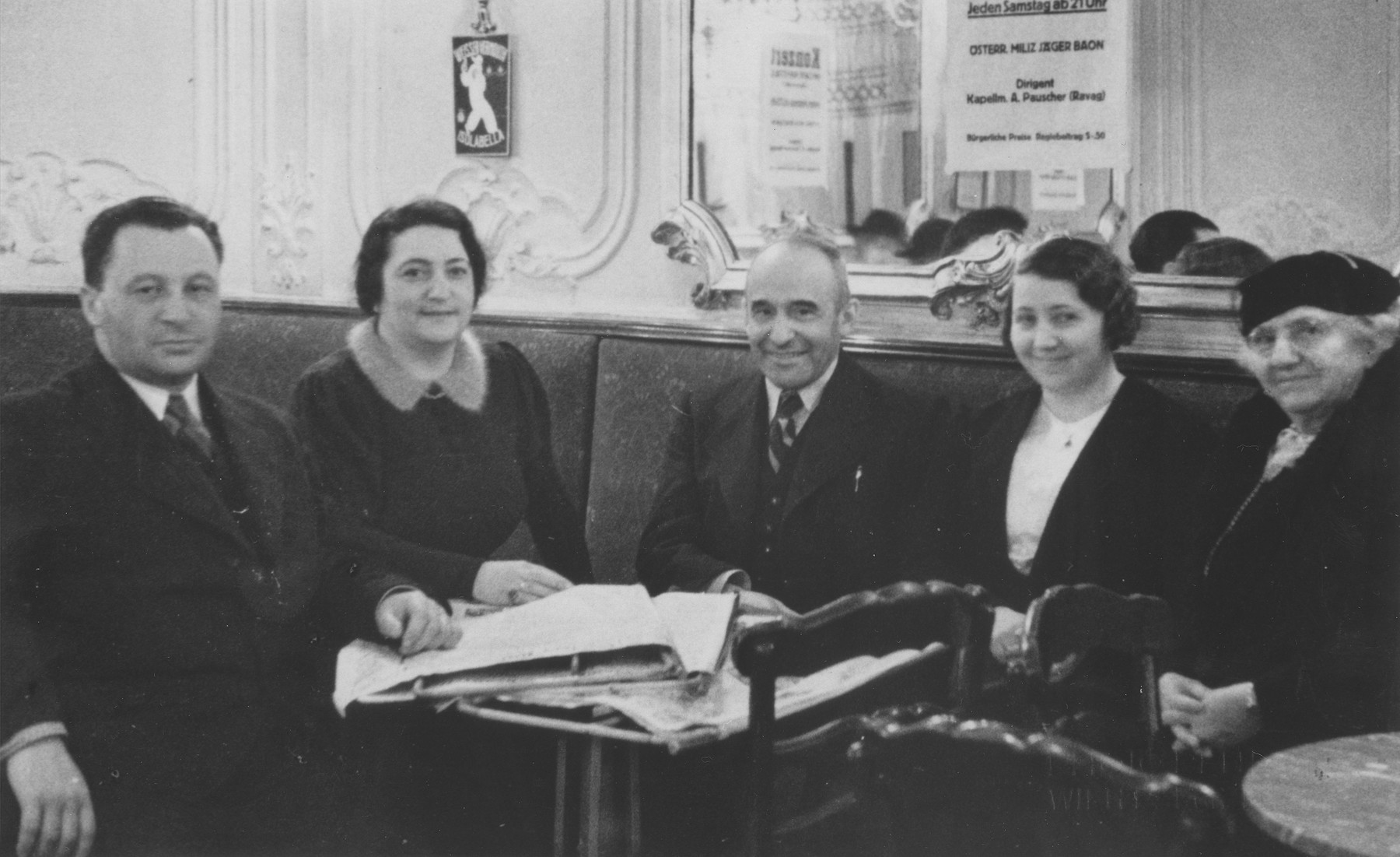 Greta and Arthur Mayer (second and third from the right) sit at a table with friends in their coffee house in Vienna.