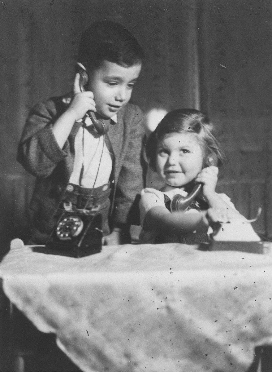 Five-year-old Bedrich Deutsch talks on a toy telephone to his friend Eva Nassau.  Eva Nassau is the daughter of a Jewish lawyer who was a friend of the Deutsch family.  She survived the war.