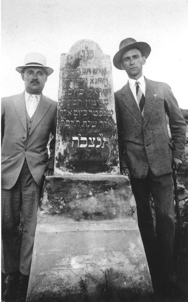 Two members of the Katz family pose next to the tombstone of a relative in a Jewish cemetery in Vilna.