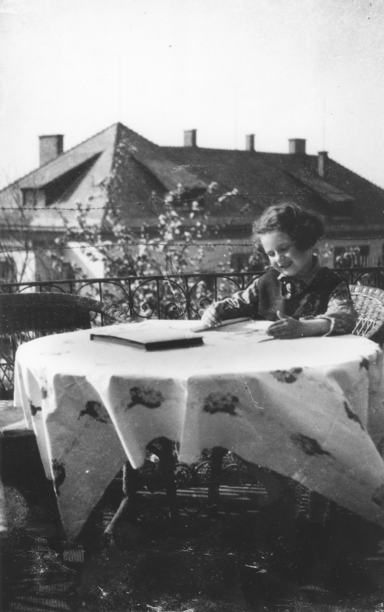 A young Jewish girl sits at a table on the porch of her home.  Pictured is Zuzana Brunnova.