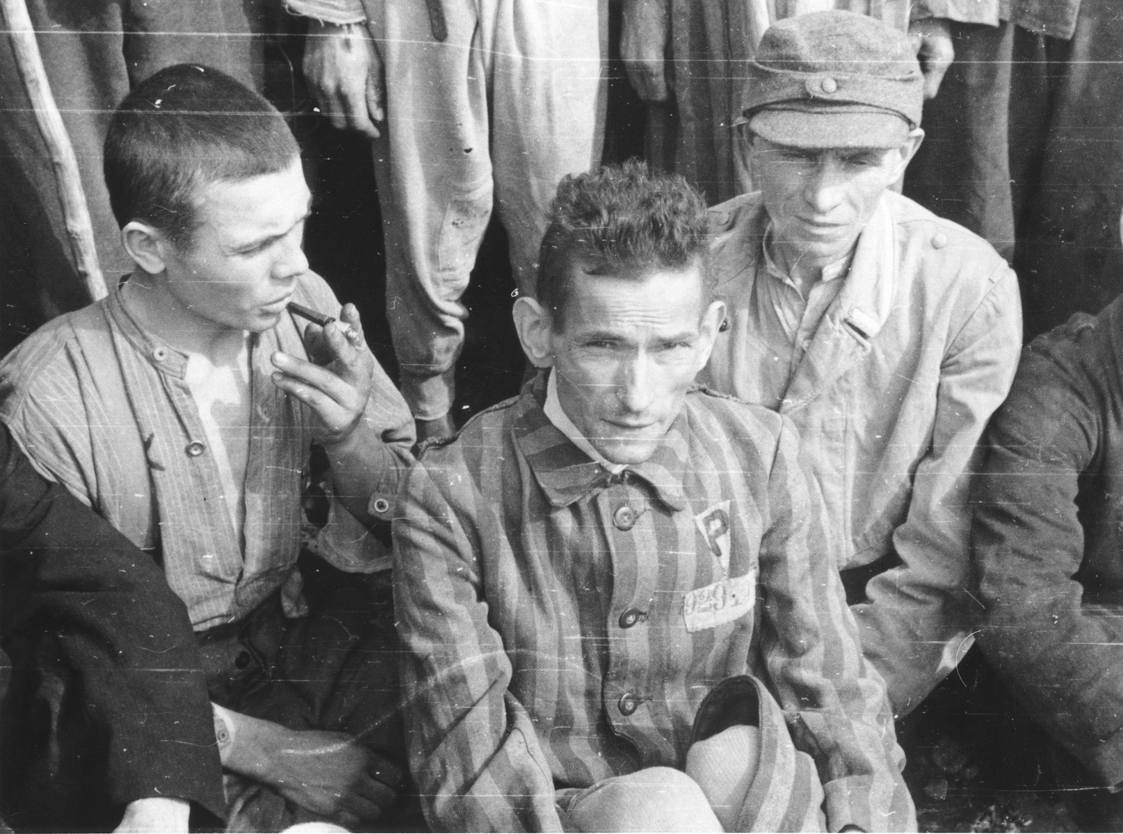 A close-up of three survivors at a gathering in the Langenstein-Zwieberge concentration camp, a sub-camp of Buchenwald, soon after liberation.  The man in the foreground wears a triangular badge with the letter P probably signifying that he was classified as a Polish political prisoner during his incarceration in the camp.