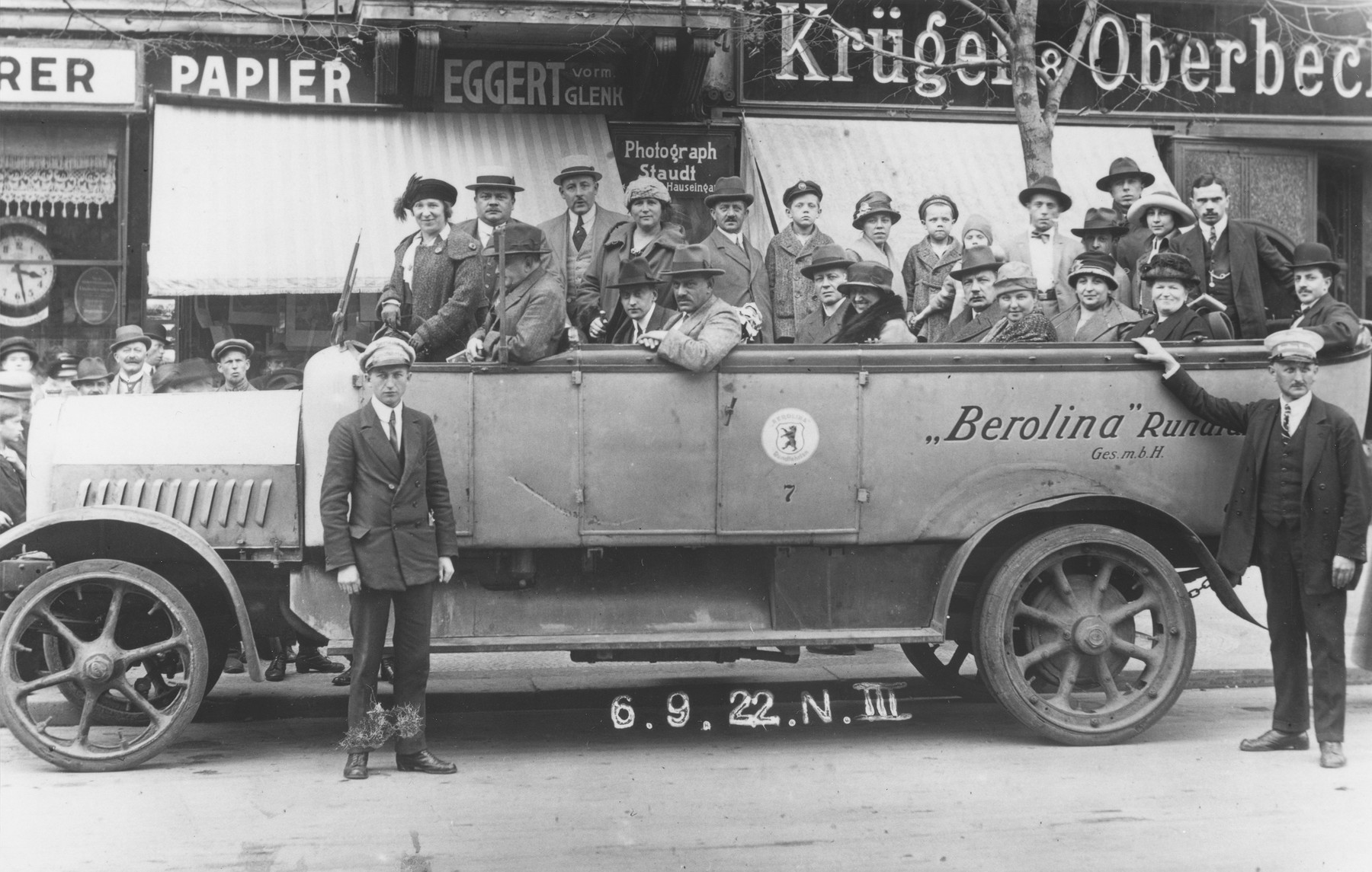 Dr. Adolf Huber and his wife, Paula (Knopfmacher) Huber, ride in the back of an open bus during a tour of Berlin.  The couple is pictured in the center of the vehicle behind the coor with the seal.