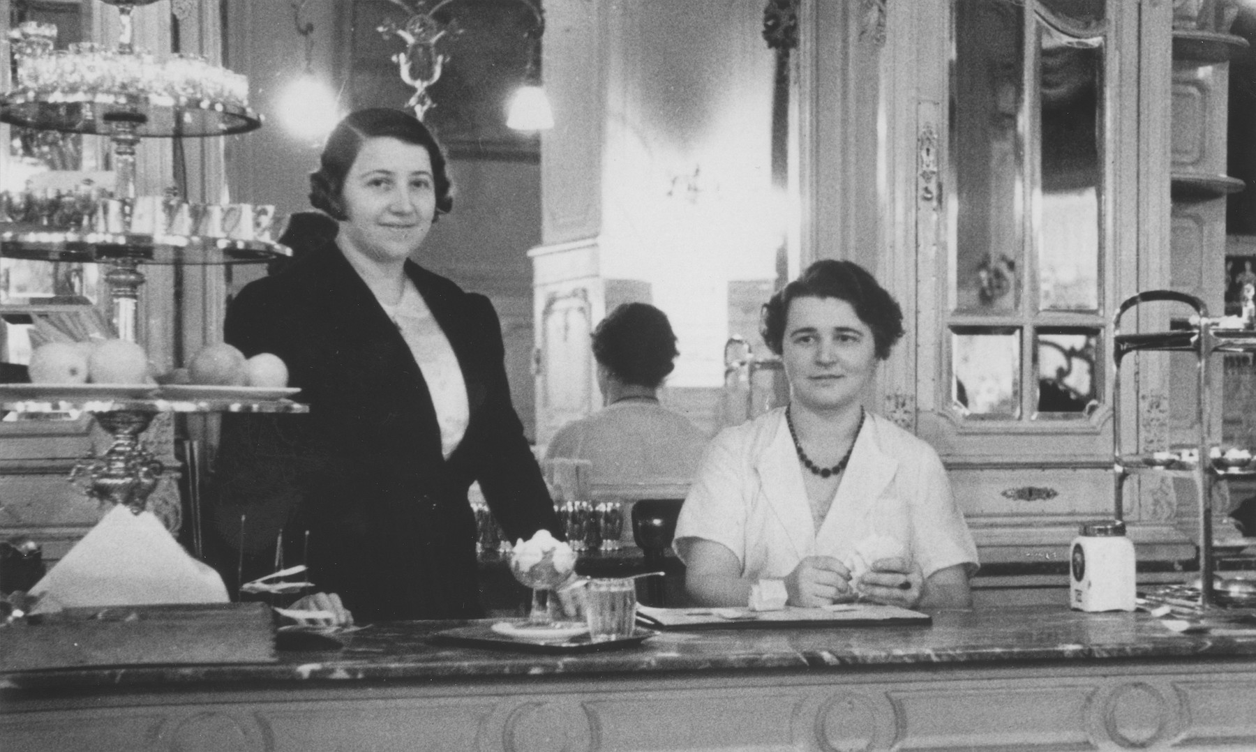 Jewish restauranteur Greta Mayer (left) stands behind the counter at her coffee house in Vienna.