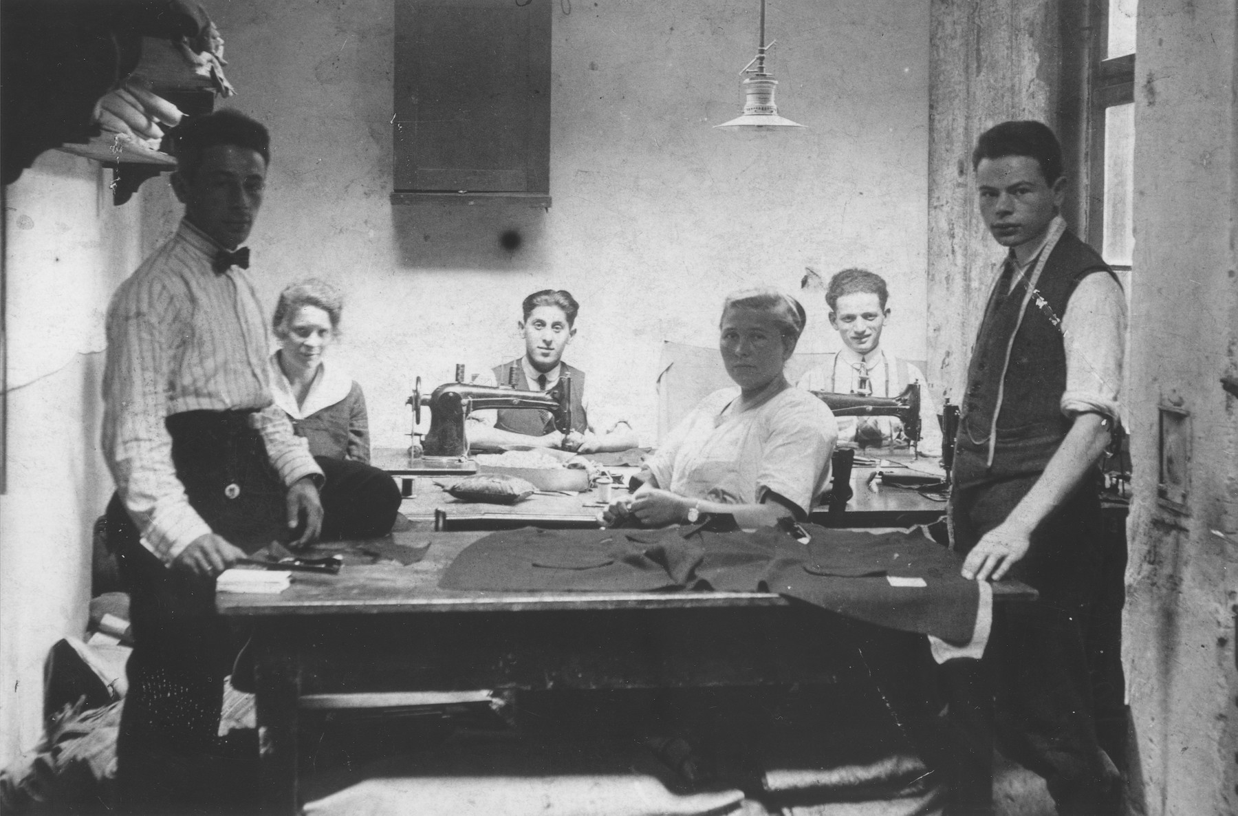 Jews at work in a tailor shop owned by Natan Wolf Lewkowicz in Bedzin, Poland.  Among those pictured is Natan Wolf Lewkowicz, the donor's father.