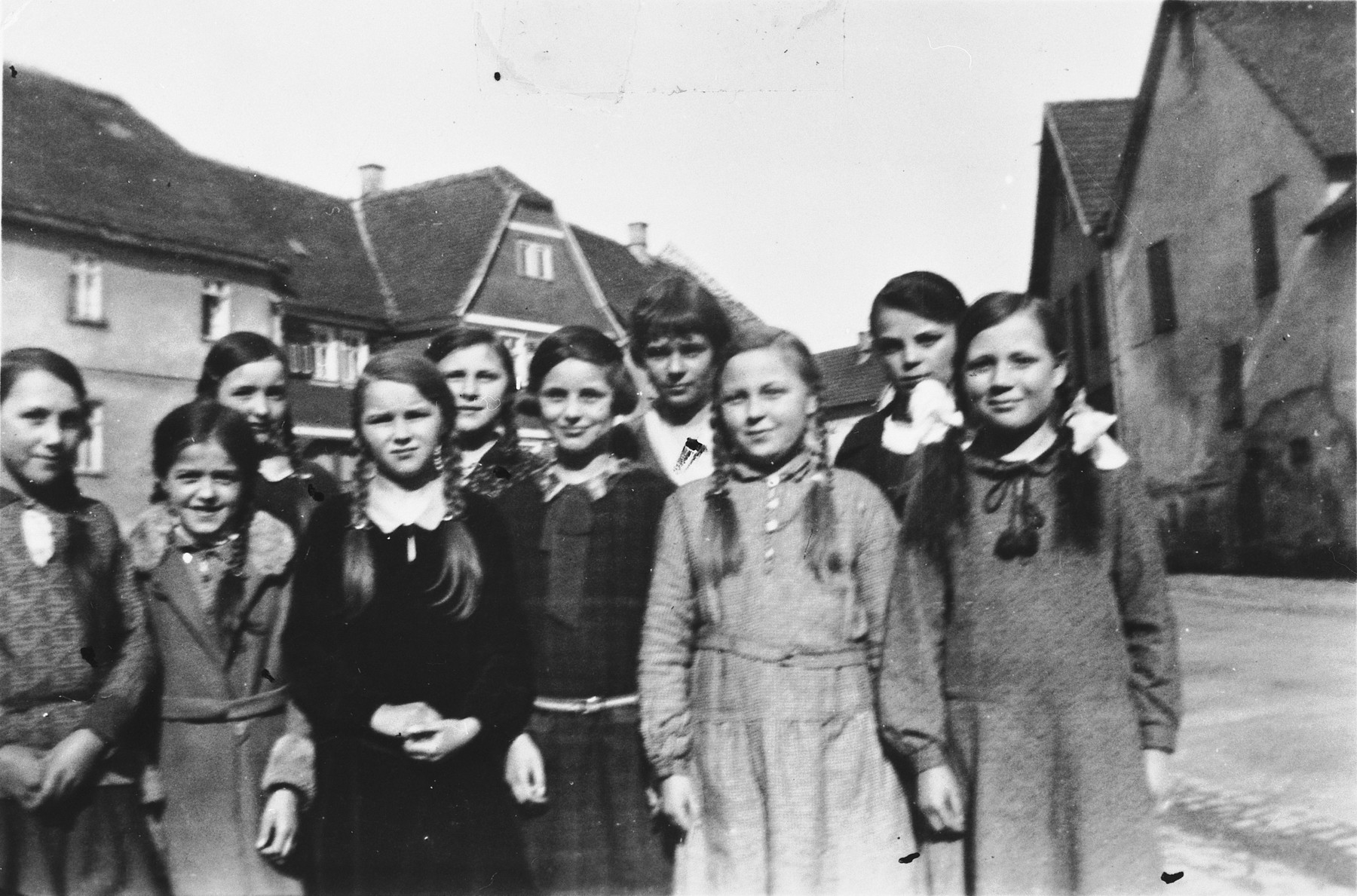 School girls, both Jewish and German, pose in a row on a street in Holzheim, Germany.  Pictured in the center is Ruth Herz.