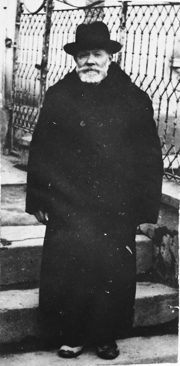 Nachman Aschkenase stands in front of the steps to a building.