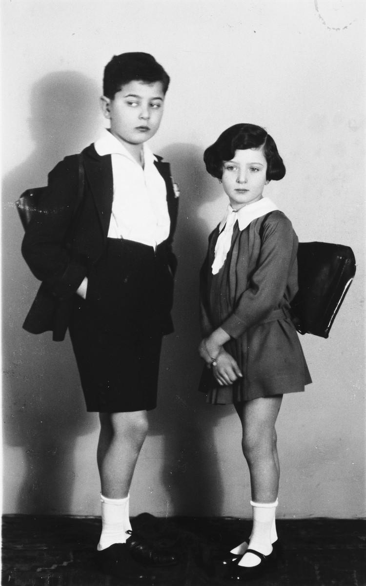 Studio portrait of two Jewish siblings wearing their school backpacks.  Pictured are Jiri and Hana Fuchs.
