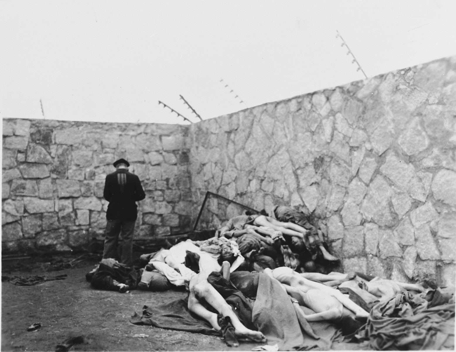 A survivor stands beside corpses piled against a wall in the Mauthausen concentration camp.