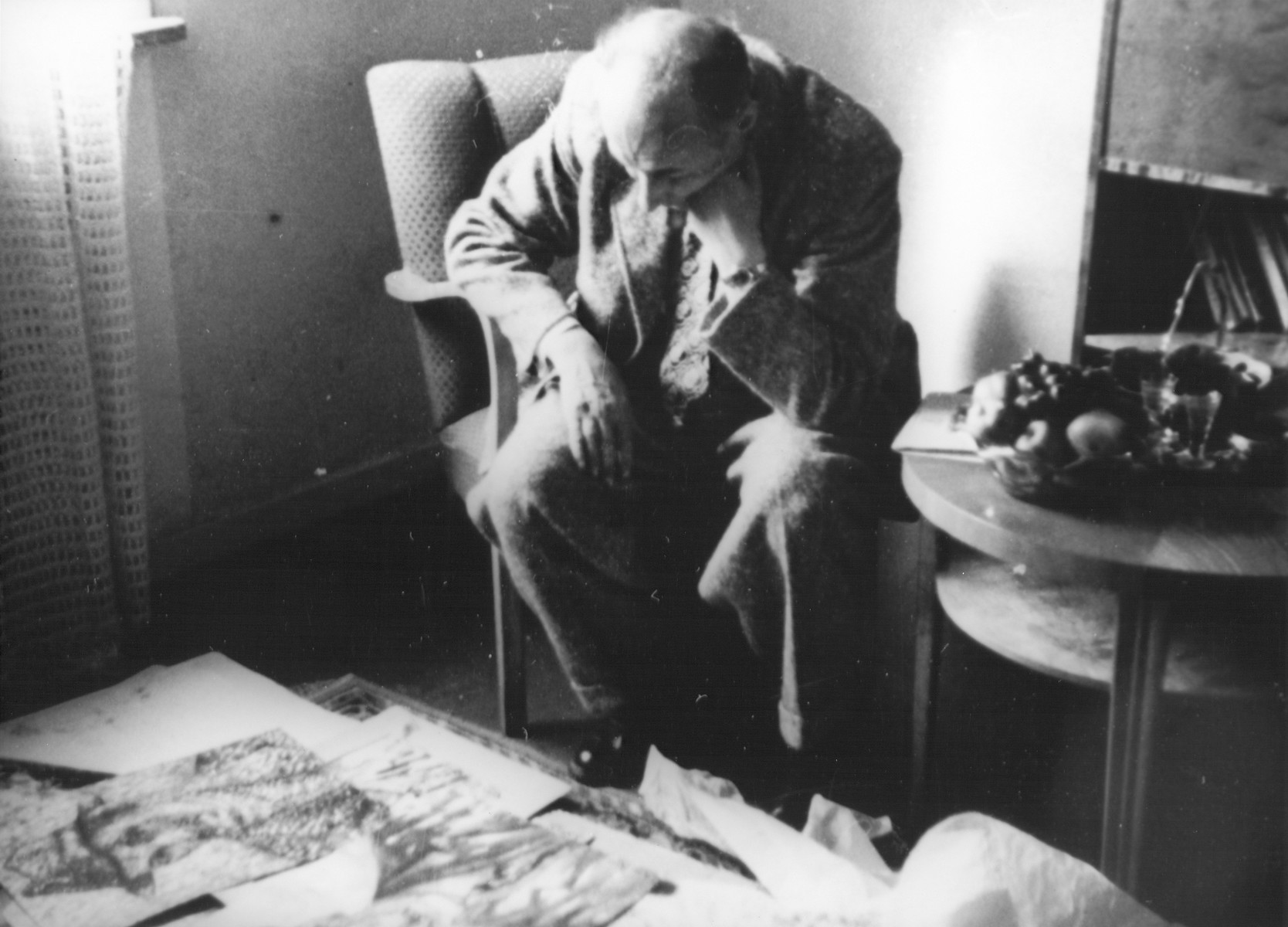 In the apartment of Nachman Zonabend, Lodz ghetto artist Josef Kowner looks at a collection of forty-five of his paintings that were rescued by Zonabend from the ghetto.   Josef Kowner died in Sweden in 1968.