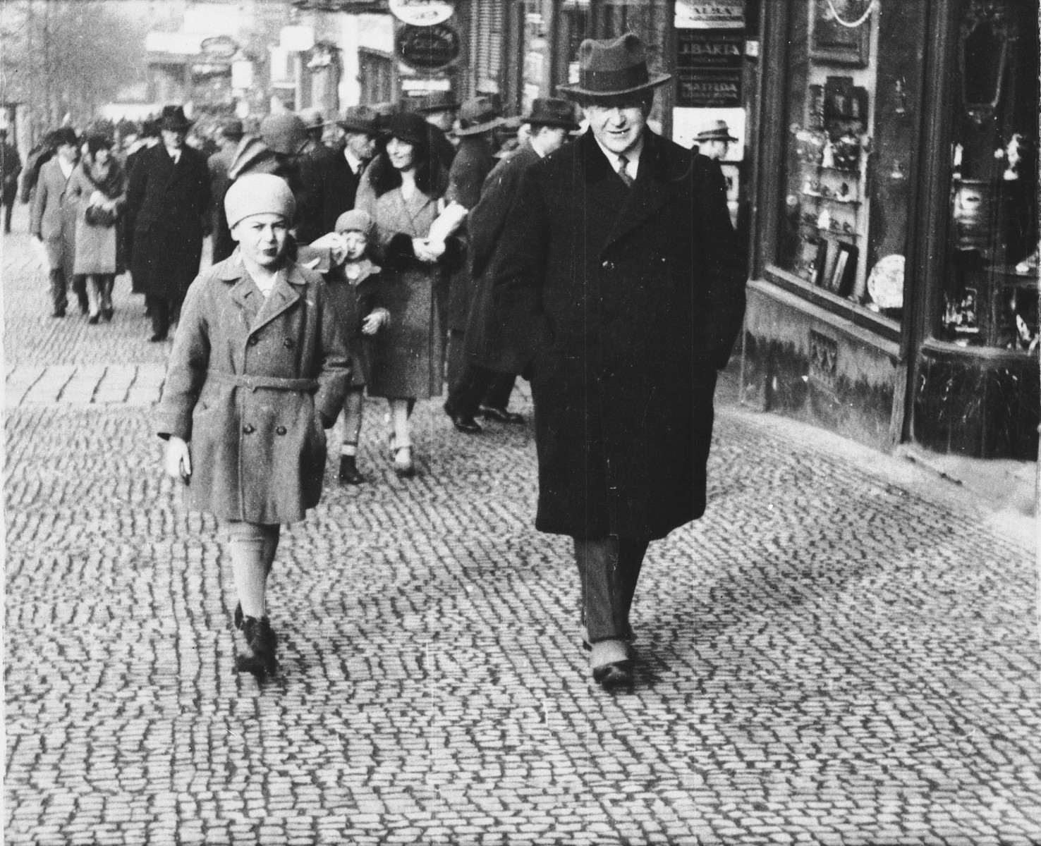 A Jewish father and son walk along a commercial street in Prague.  Pictured are Oskar and Jiri Fuchs.