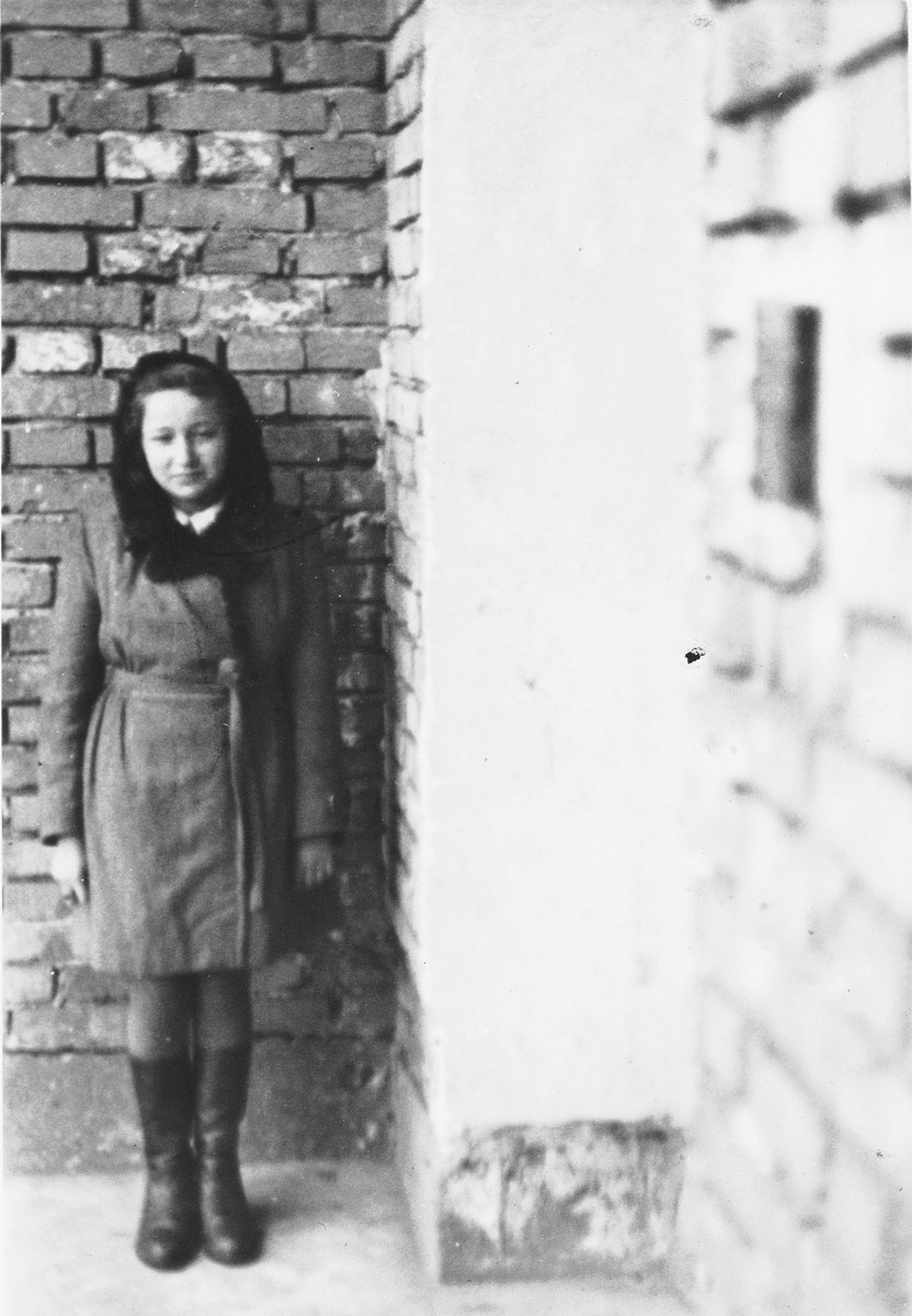 Lea Rein poses by a brick wall in Krakow after the war.