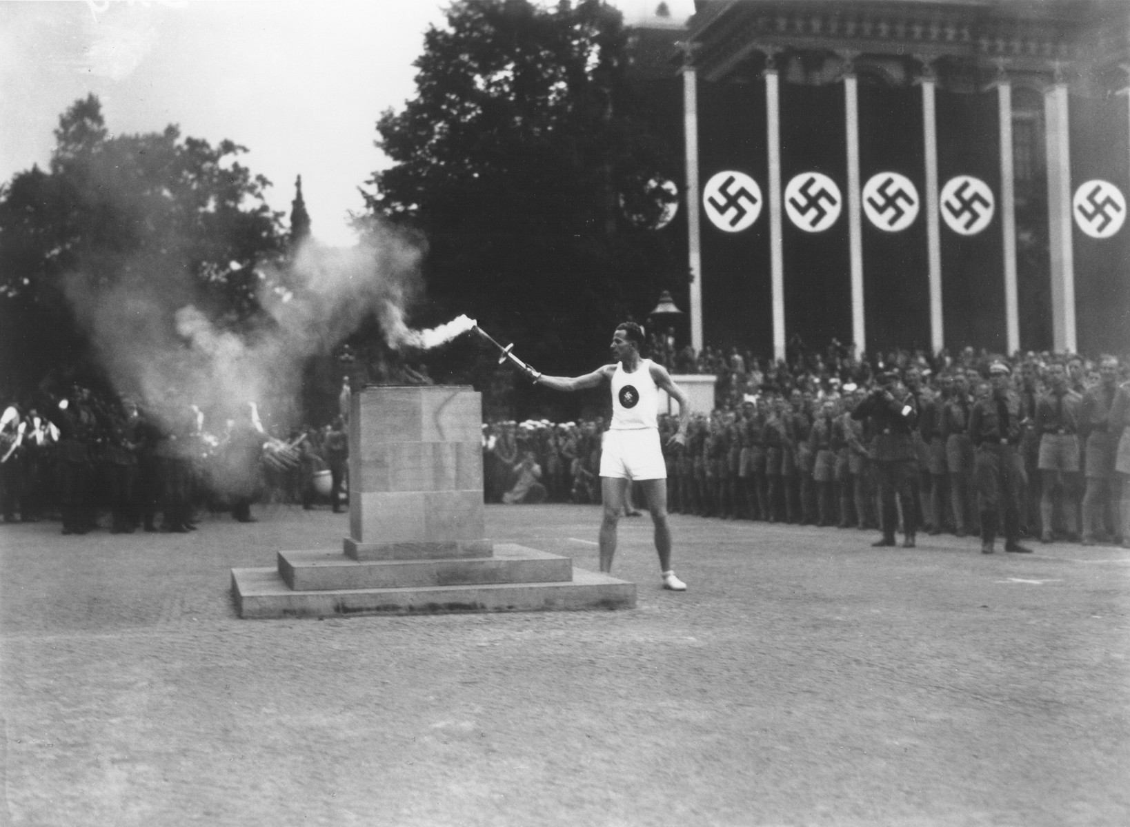 The last of the 3000 runners that carried the Olympic torch from Olympia, Greece, lights the Olympic Flame in the Lustgarten in Berlin to start the 11th Summer Olympic Games.