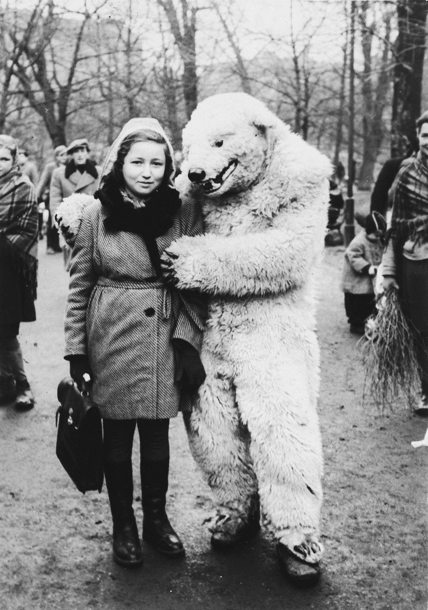Lea Rein poses with a bear mascot in a park in Krakow after the war.