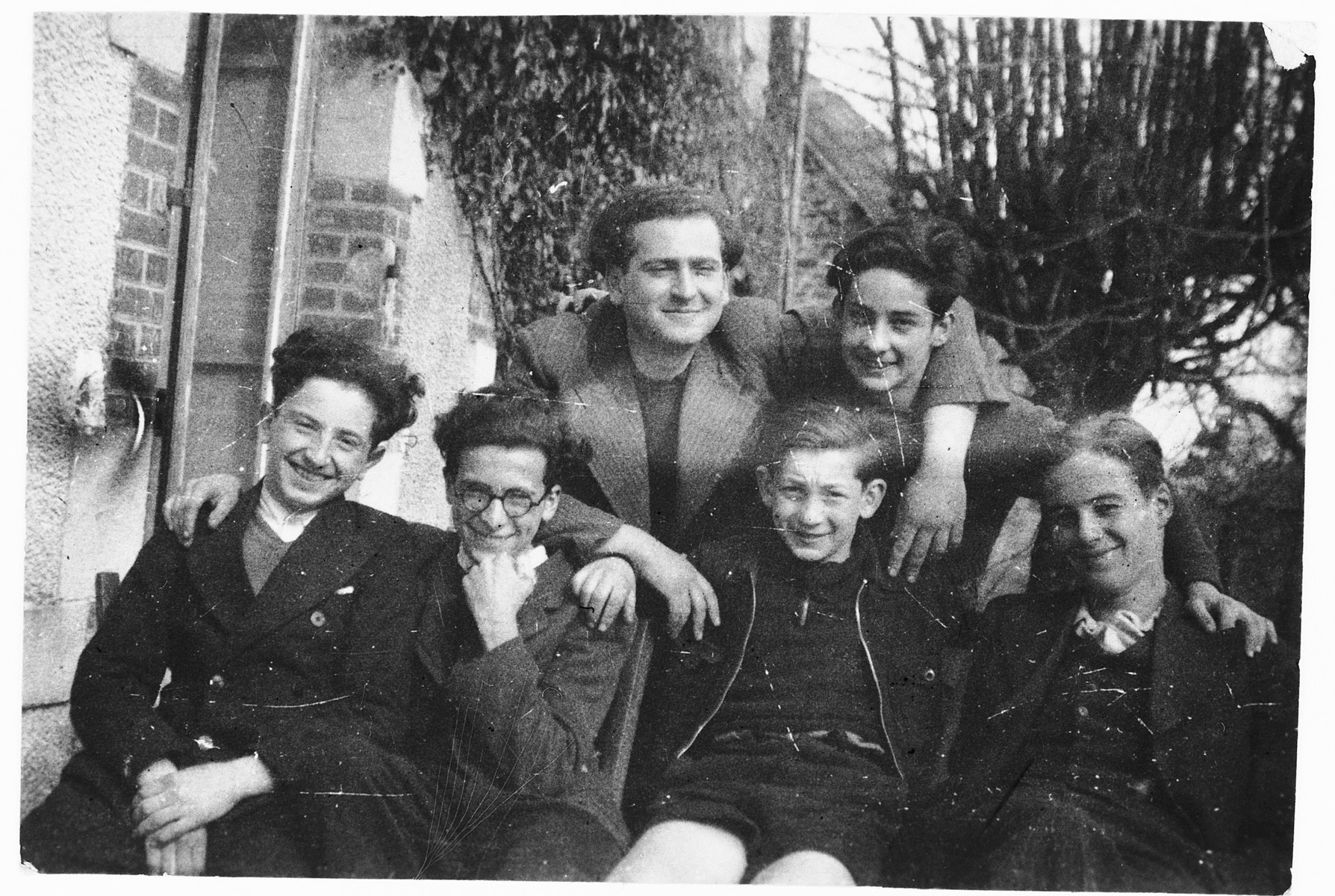 Jewish teenagers pose outside on the steps of the Chabannes children's home.   Pictured from left to right are Eryk Goldfarb, David Kenig, Budnik, Wolfgang Blumenreich.  Back row: Simon Mangel (a teacher) and Ernest Rosner.