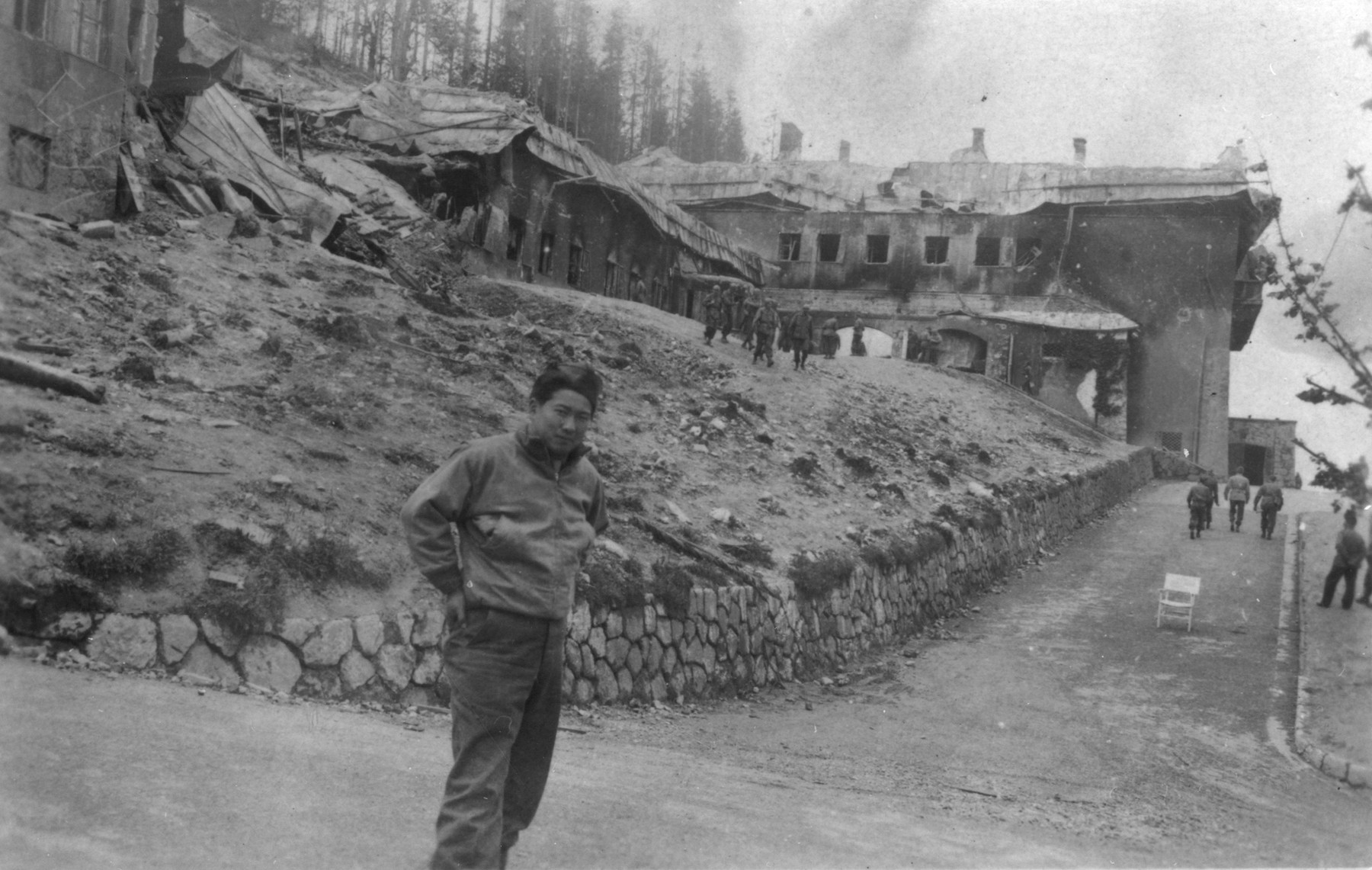 A Japanese-American soldier poses outside the destroyed Berghof, Hitler's mountain retreat in the Bavarian Alps.