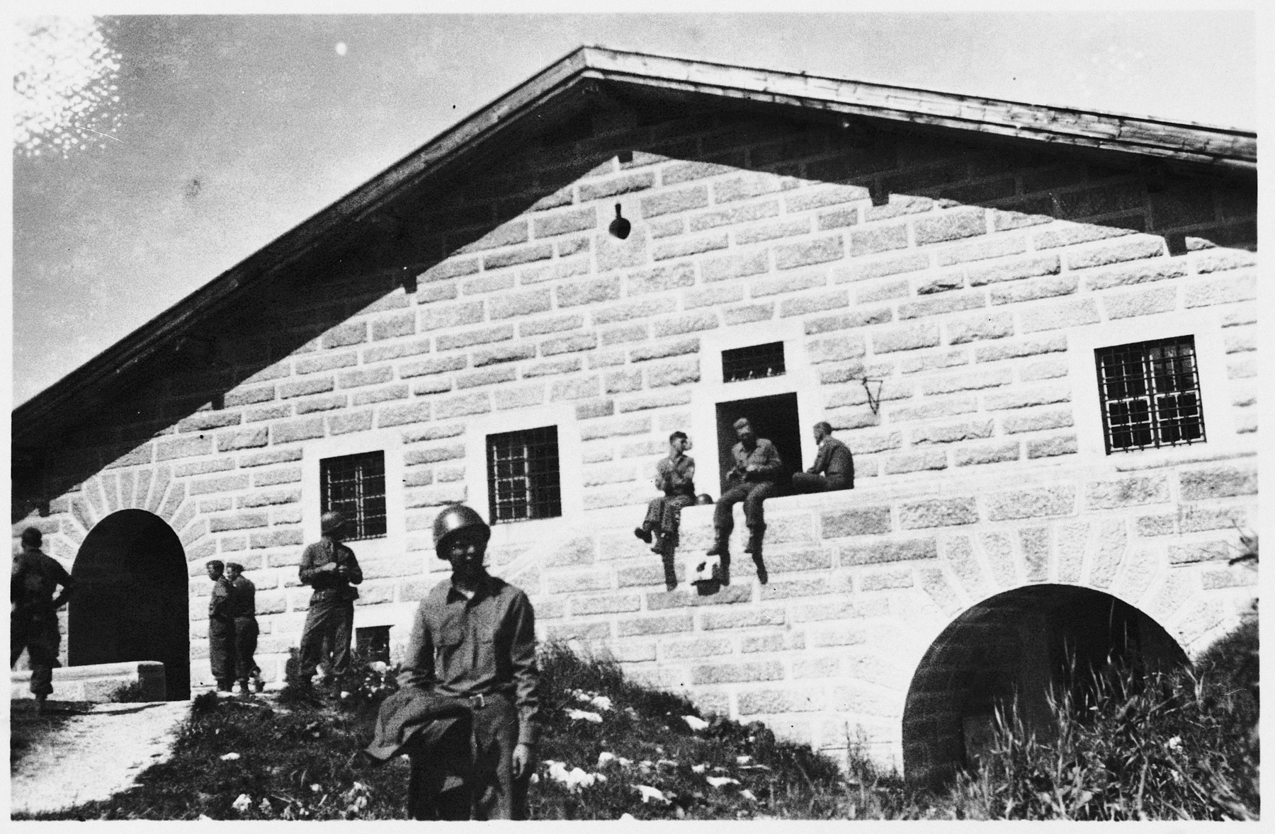Japanese-Americans with the 522nd Field Artillery Battalion pose outside the destroyed Berghof, Hitler's mountain retreat in the Bavarian Alps.