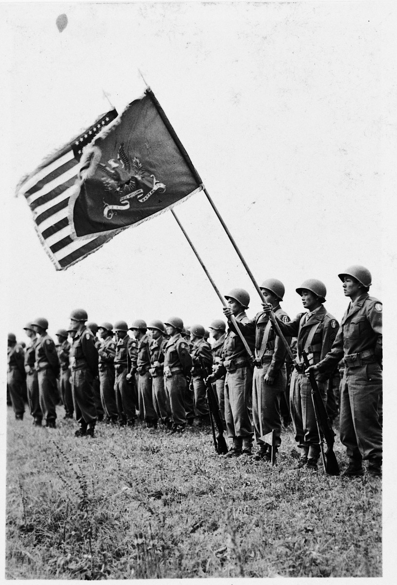 Members of the 522nd Field Artillery Battalion in Germany stand in formation with the American and battalion flags.