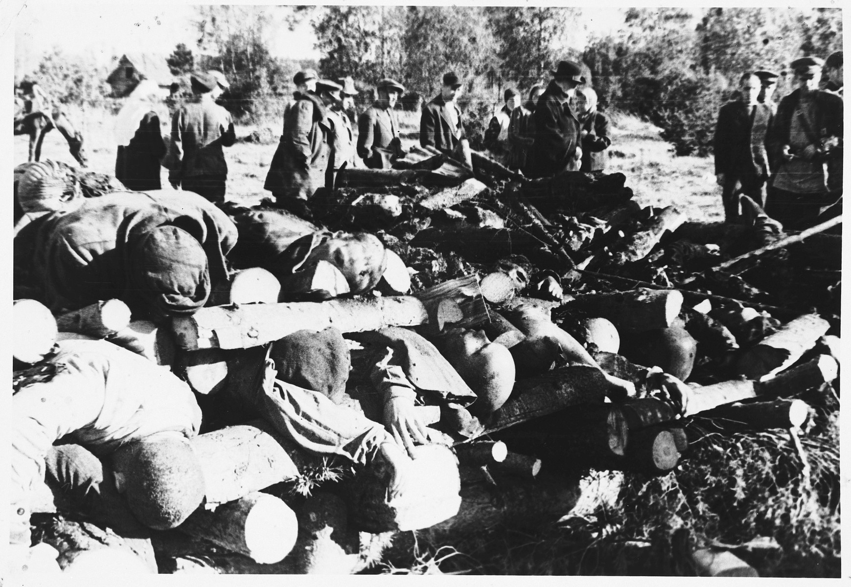 Soviet soldiers observe recently burned corpses on the grounds of the Klooga concentration camp.