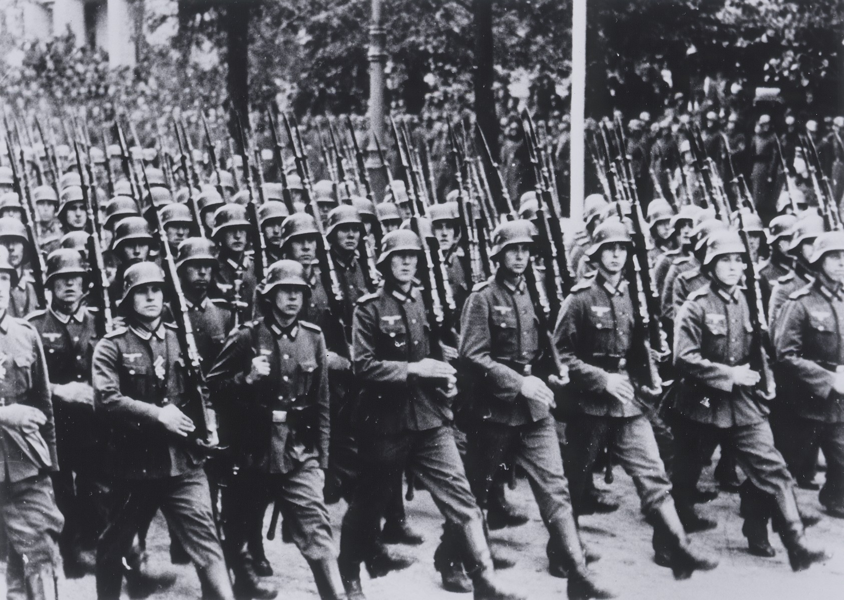German soldiers march into Warsaw carrying bayonets.