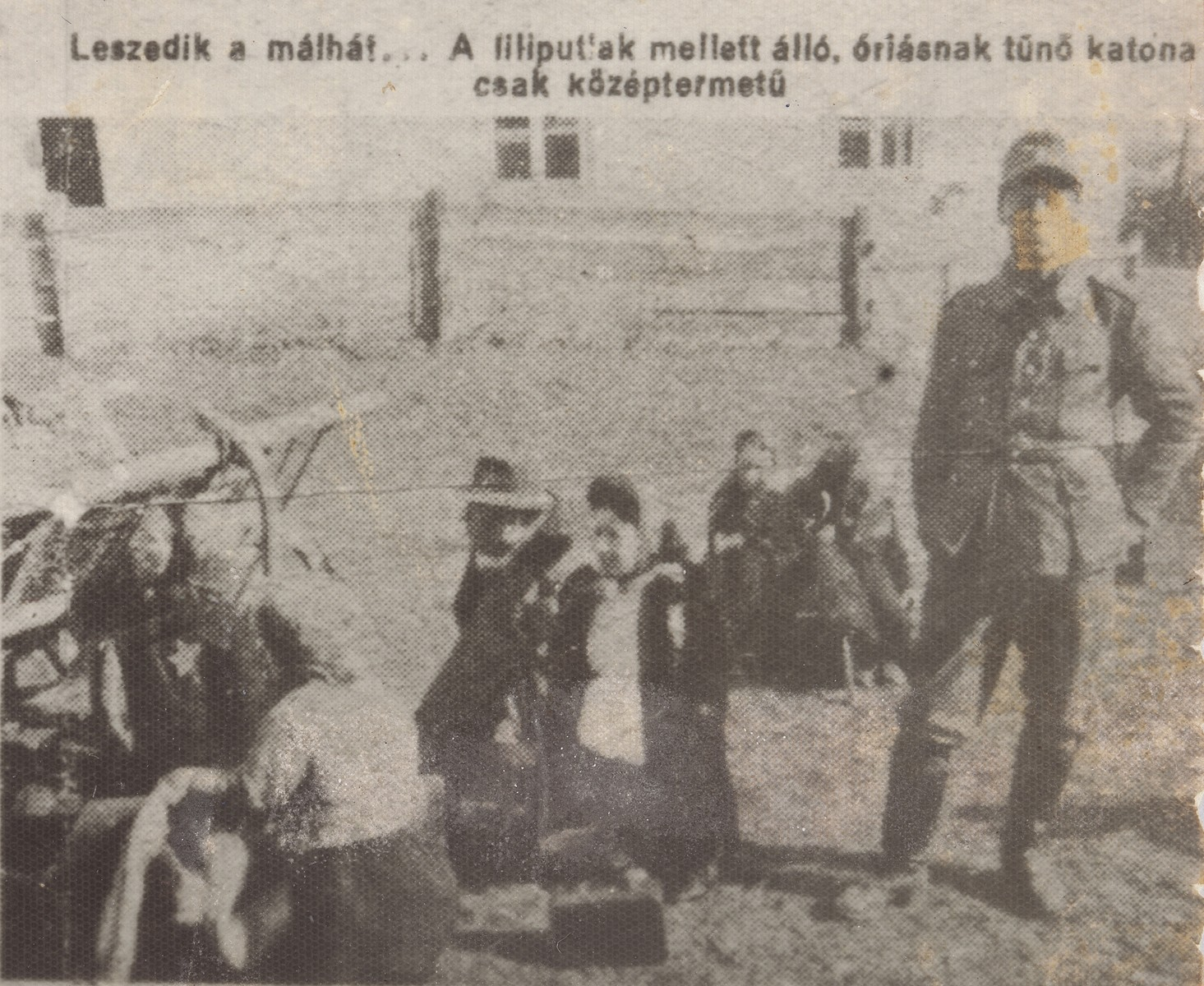 """A German soldier stands next to a group of Jewish dwarves as they remove their bundles from a farm wagon.  The dwarves are members of the Ovici family.  The newspaper caption reads: """"They take their bundles from the cart... the soldier standing next to them appears to be a giant, even though he is only of average height."""""""
