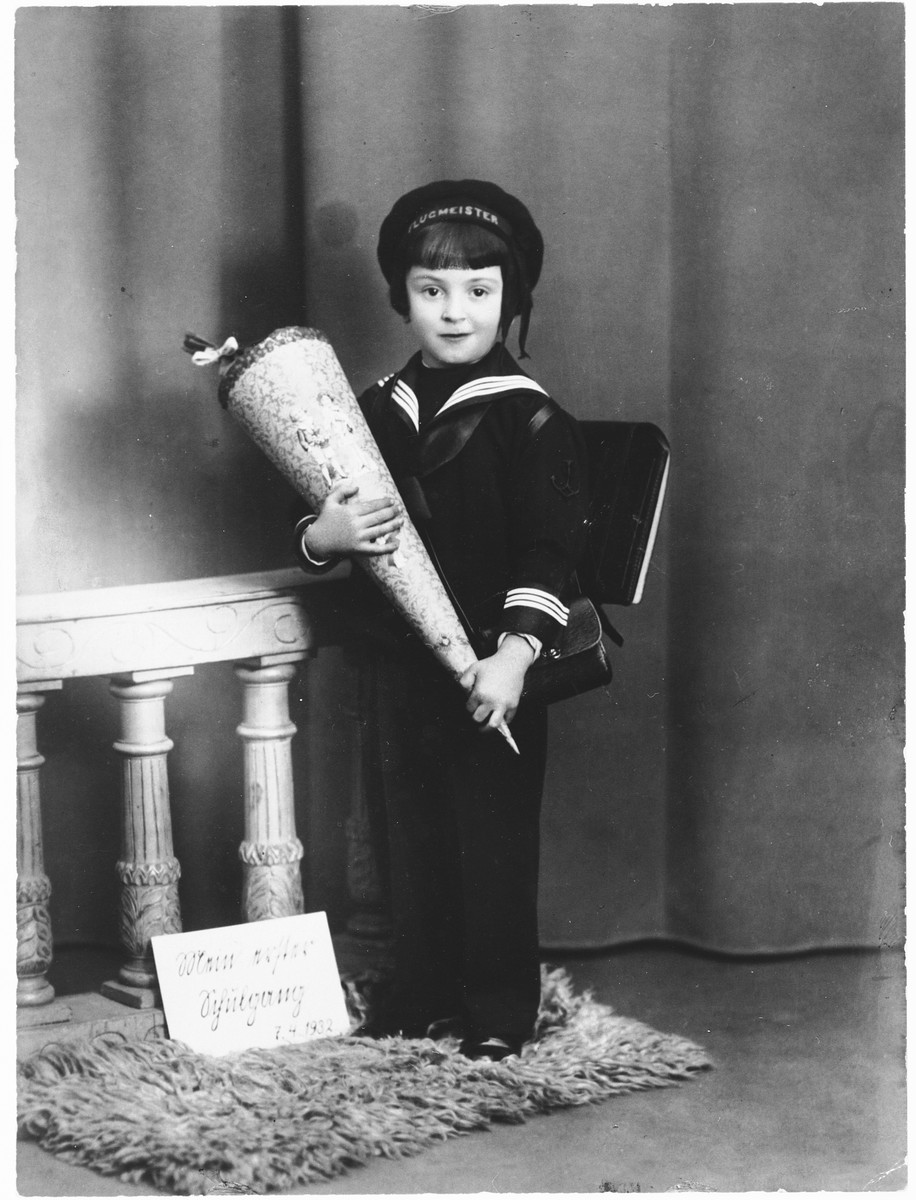 Studio portrait of a Jewish child holding a cone filled with candy on his first day of school in Berlin.  Pictured is Eryk Goldfarb.