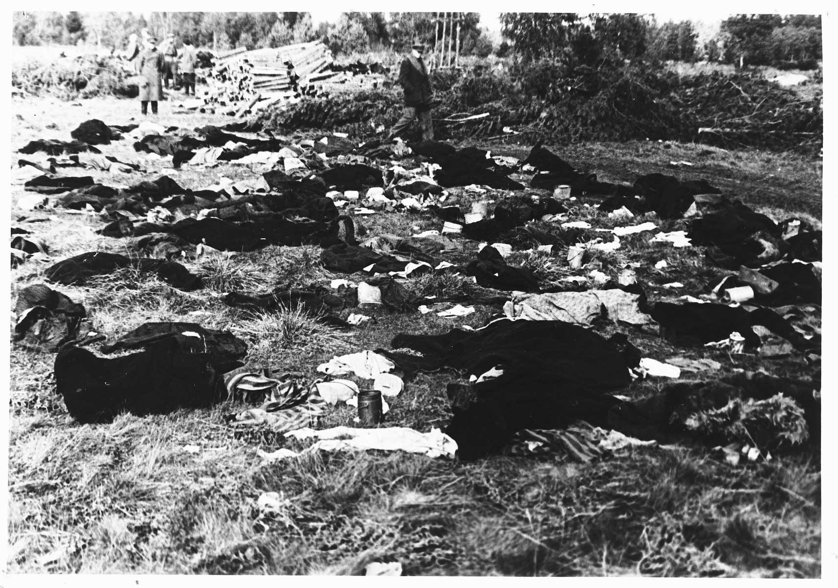 Soviet soldiers observe burned corpses lying on the grounds of the Klooga concentration camp.