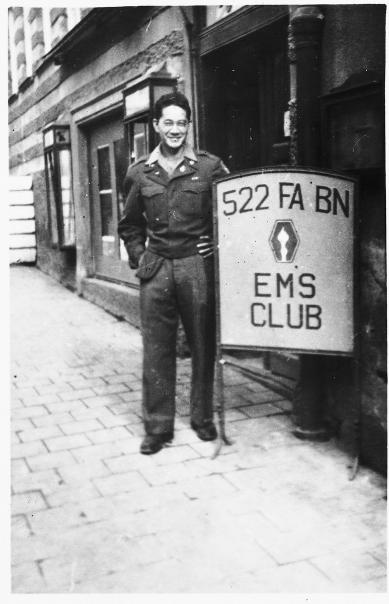 Clarence Matsamura, a Japanese-American soldier in the 522nd Field Artillery Battalion in Germany, poses next to a 522 EMS club sign.  Matsamura was the soldier who liberated Jewish survivor Solly Ganor from a death march in Waakirchen.