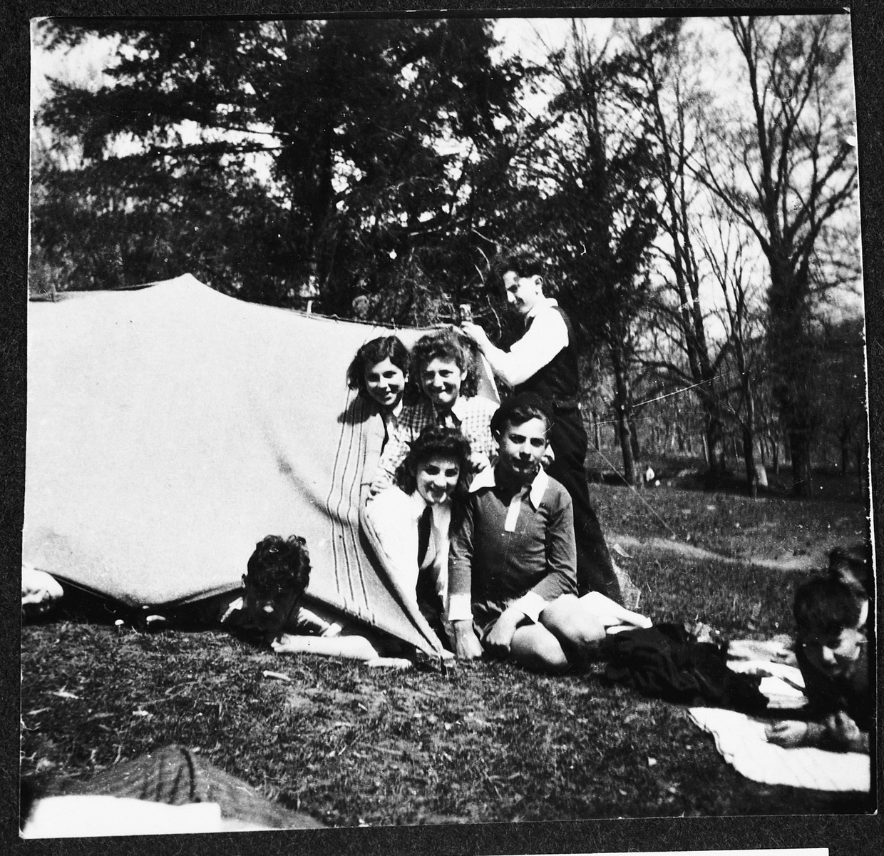 Jewish refugee children from the Chabannes OSE [Oeuvre de Secours aux Enfants] children's home pose at the entrance to a blanket tent while on a camping trip.