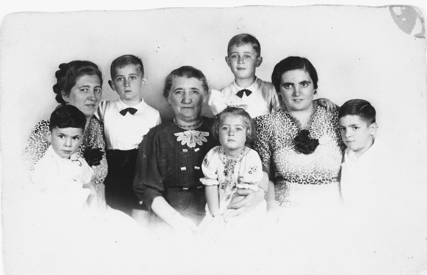 """Prewar portrait of a Jewish family.  Pictured in the center is Sophia (nee Wolff) de Jong.  Her daughtersJudith (""""Juul"""") (nee de Jong) Vos and Louise (""""Wies"""") (nee de Jong) Israels are pictured on the left and right, respectively.  Judith's children are Hans and Louk (pictured in  standing in the back, left and right respectively), and Phia (on her grandmother Sophia's lap).  Louise's children are Loekie (front, far left) and Nico (front, far right)."""