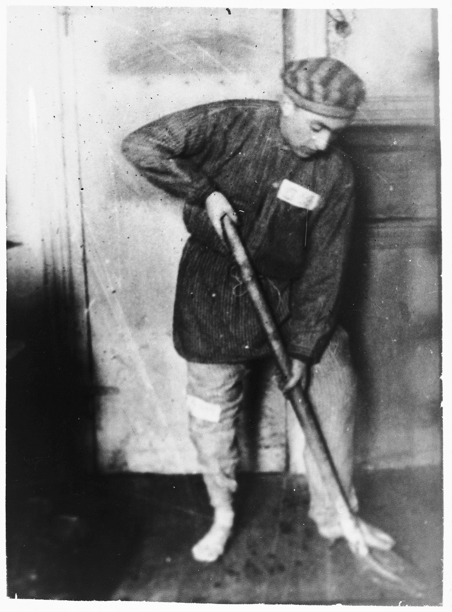 A Jewish prisoner mops the floor of a cell in the Klooga concentration camp.