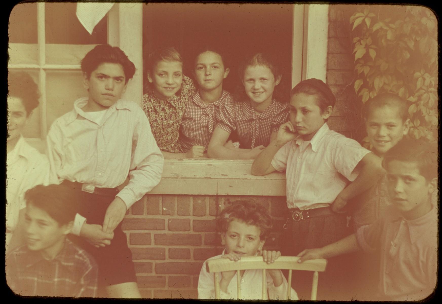 Jewish DP children pose in and around the window of the Kibbutz Ilaniah children's home in Apeldoorn.