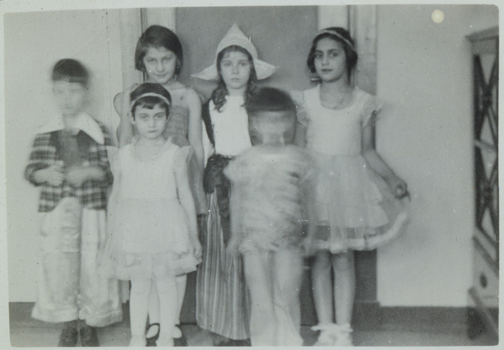 Group portrait of Jewish children wearing costumes for the Purim holiday.  Pictured from left to right are: unknown; Anne Frank; Evelyn Werthauer; Barbara Ledermann; unknown; Margot Frank.