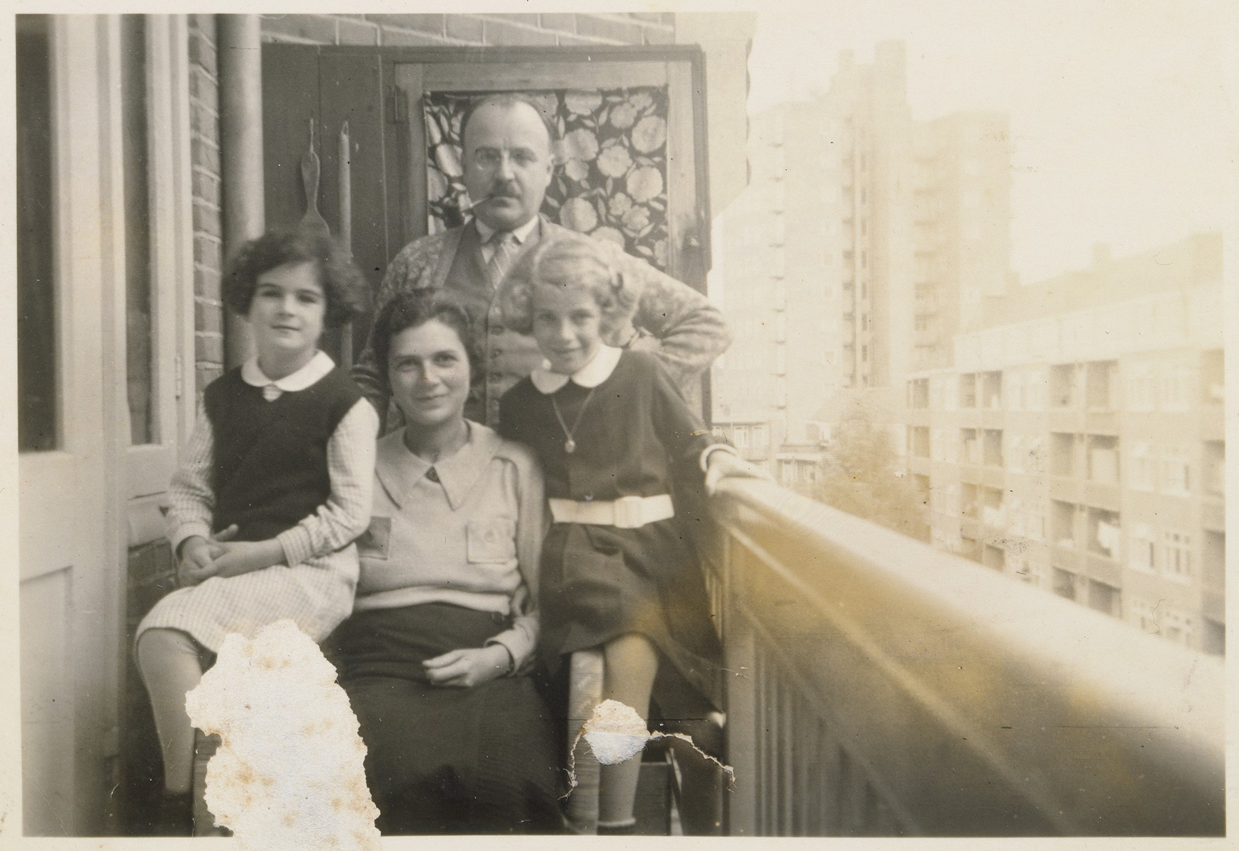 Members of the Ledermann family, Jewish refugees from Berlin, pose outside on the terrace of their apartment in Amsterdam.  Pictured are Franz and Ilse Ledermann and their two daughters, Barbara and Susanna.