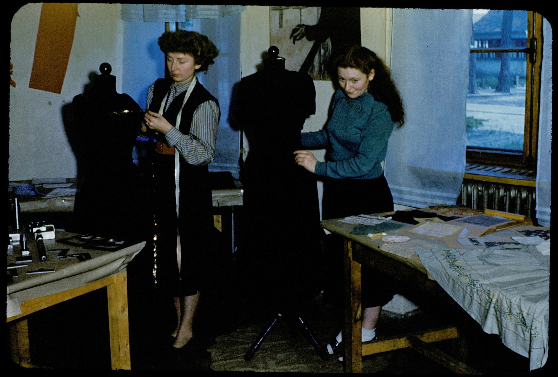 Women learn dressmaking at an ORT vocational training school in the Foehrenwald displaced persons camp.  Standing on the right is Brenda Maryles (nee Soroka) and the woman on the left is the instructor.
