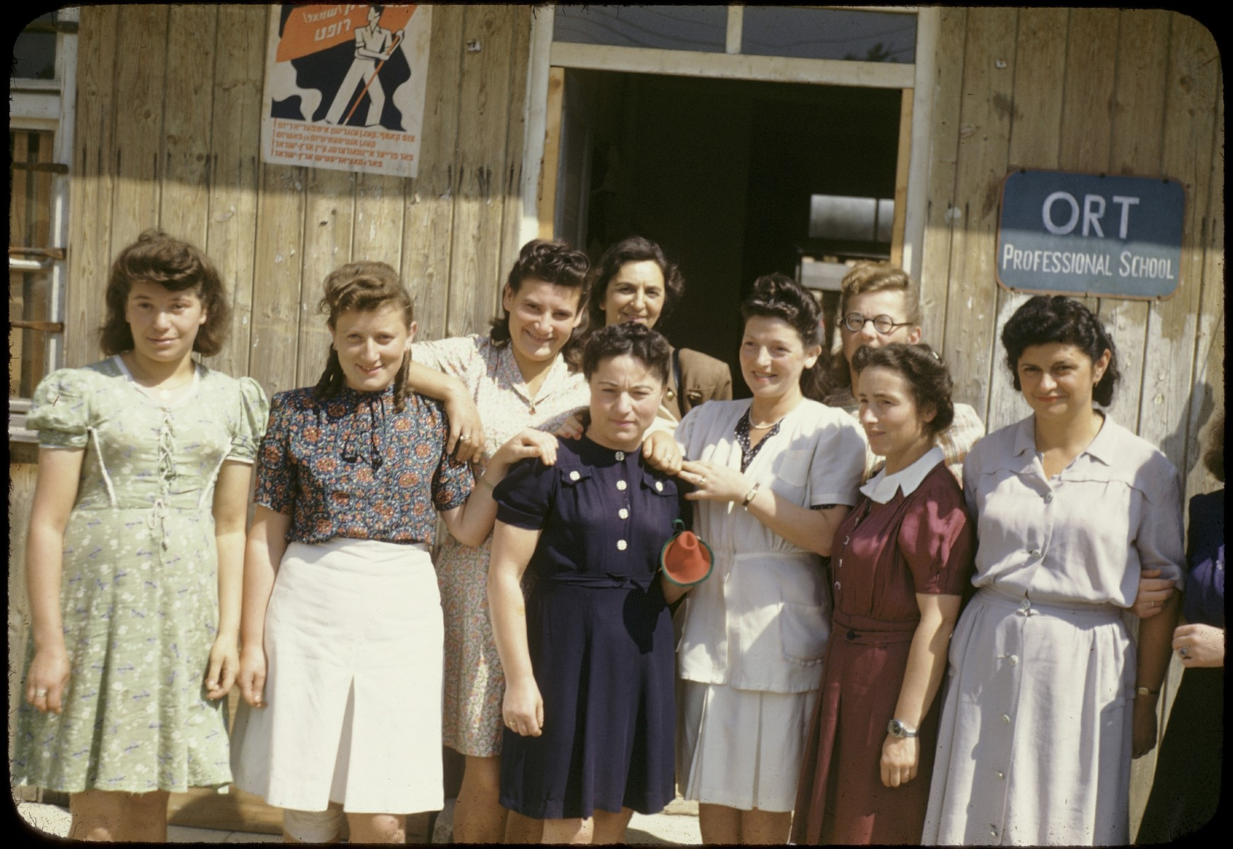 Group portrait of Jewish women standing outside the ORT school in the Feldafing displaced persons camp.  Among those pictured is Judit Ginsburg (first woman on the right).