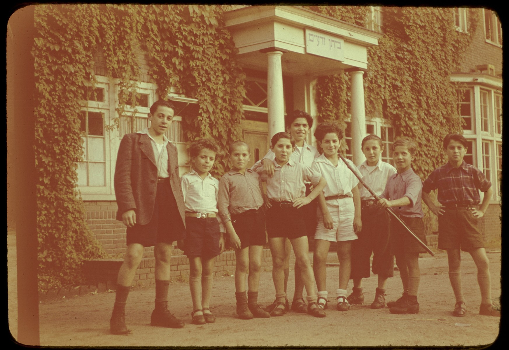 Group portrait of Jewish DP children standing outside the Ilaniah children's home in Apeldoorn. One child is holding a wooden bow, an arrow at his feet.