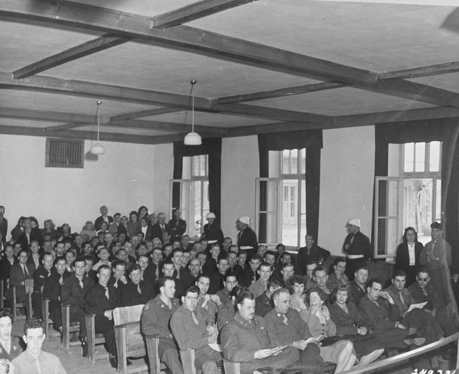 Spectators await the return of the judges for sentencing during the trial of 74 SS men charged with perpetrating the Malmedy atrocity.