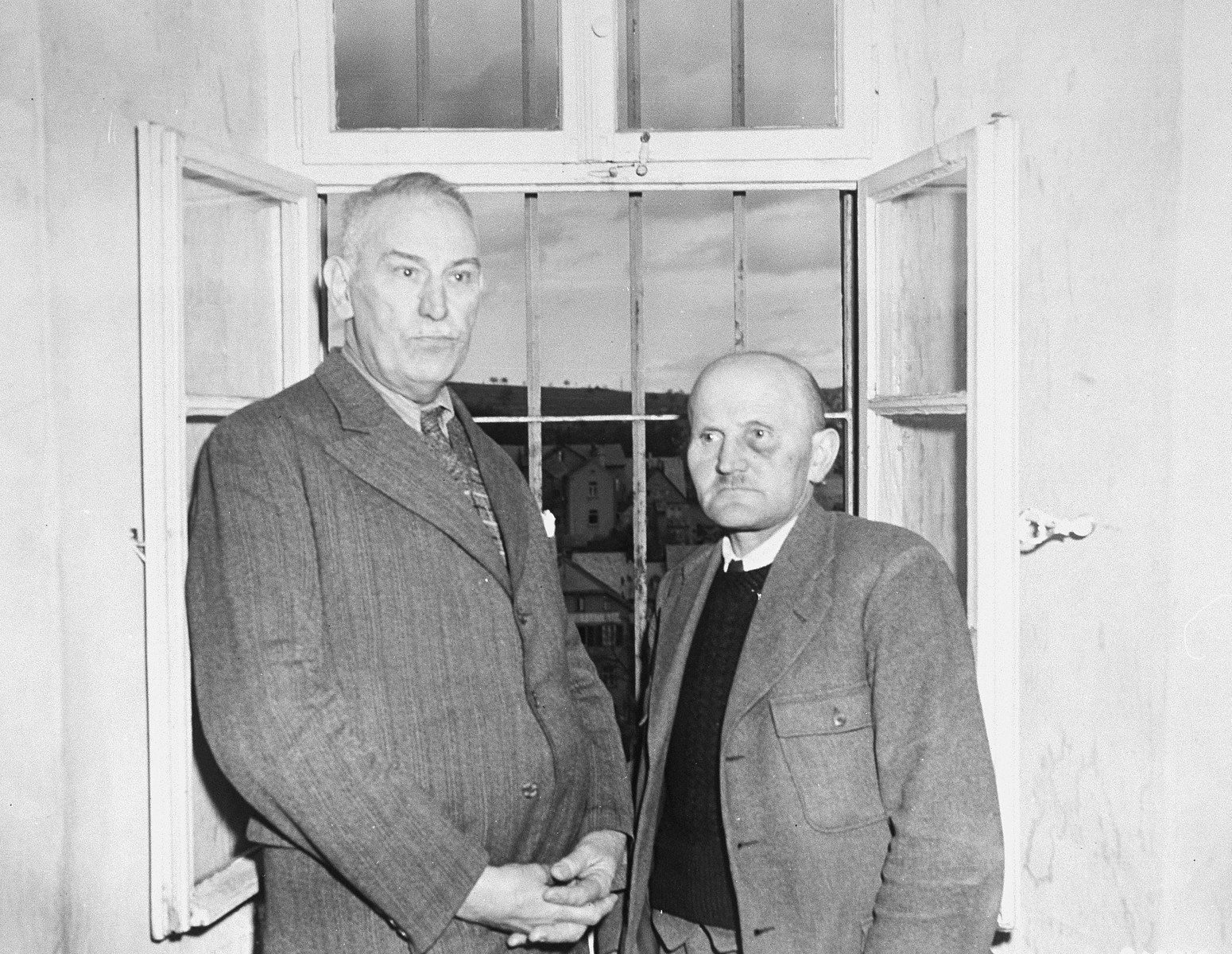 Dr. Adolf Wahlmann (left), chief physician at the Hadamar Institute, and Karl Willig (right), assistant male nurse, pose next to a barred window at the euthanasia facility where they are being held prisoner by American authorities.  The photograph was taken by an American military photographer soon after the liberation.