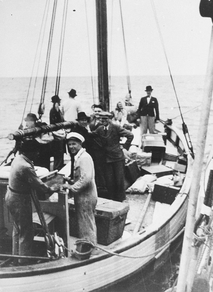 "Danish fishermen (foreground) ferry a boatload of fugitives across a narrow sound to neutral Sweden.    Caption from the Danish Museum reads: ""Transfer of passengers from a Danish ship to a Swedish one in the waters between Denmark and Sweden. Picture from a slideshow compiled to document the activities of the escape organisation Danish-Swedish Refugee Service run by Mr. Leif Hendil. The pictures were probably all taken shortly before the German capitulation in May 1945, and the refugees are thus unlikely to be Jewish."""