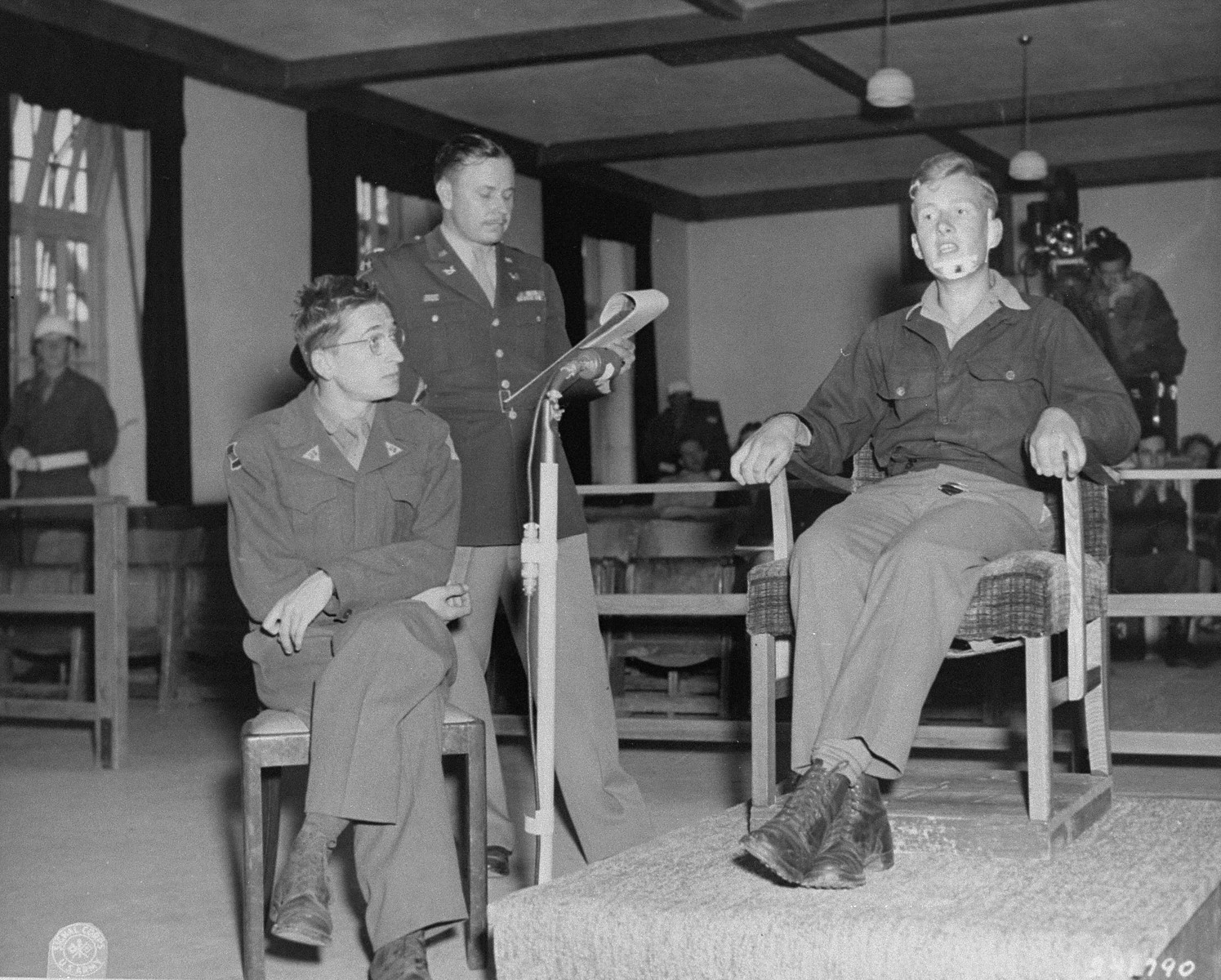 Former SS 2nd Lieutenant Kurt Kramm testifies at the trial of 74 former SS men charged with perpetrating the Malmedy atrocity.   Pictured from left to right are: Herbert Rosenstock, an interpreter; Lt. Col. Burton F. Ellis; and Kramm.
