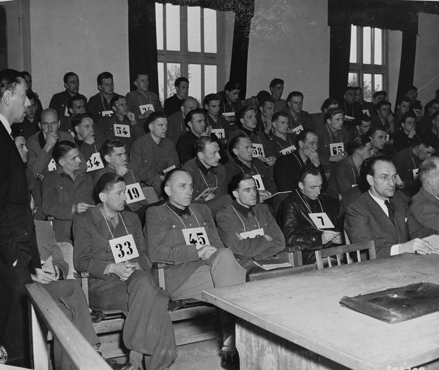 Defendants former SS General Fritz Kraemer (#33), former SS General Hermann Priess (#45), and former SS Colonel Peiper (third from the left in the first row) listen to Colonel William Everett give the defense's closing statement at the trial of 74 SS men charged with perpetrating the Malmedy atrocity.