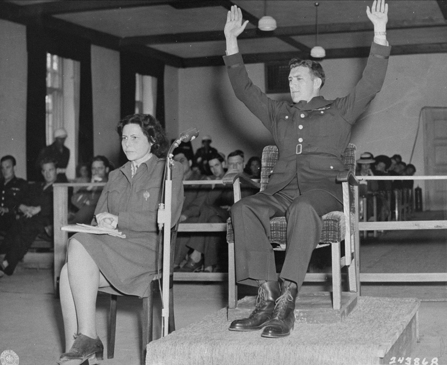 Former U.S. Army sergeant Kenneth Ahrens demonstrates how he surrendered to SS soldiers, during his testimony at the trial of 74 SS men charged with perpetrating the Malmedy atrocity.
