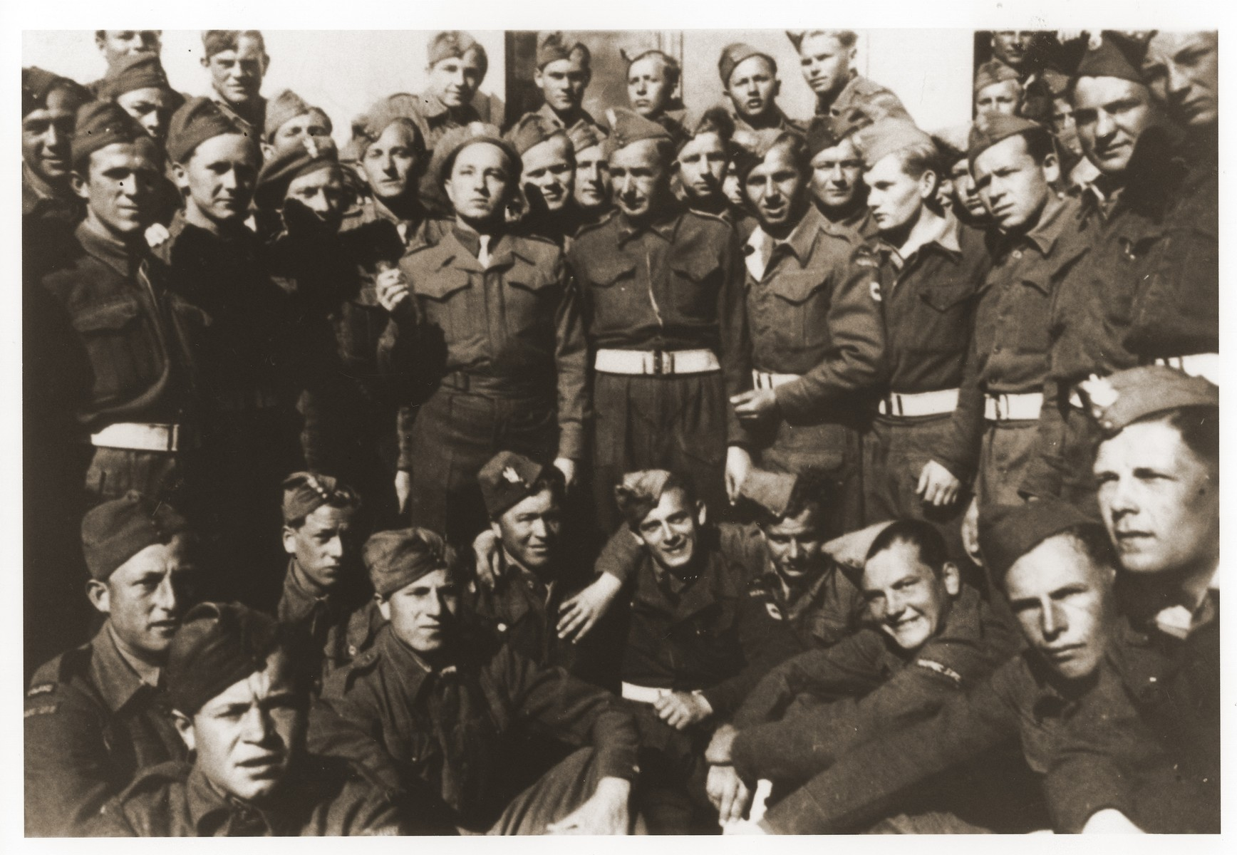 Group portrait of a unit of the Polish Home Army [Armia Krajowa].   Among those pictured is Chaim Lingalka, the donor's cousin.  Lingalka joined the AK under the alias Adam Sarna.  His unit was sent to Italy where it joined forces with the British Army.  Also pictured is Ewald Kroll (second row, third from the right) who joined the AK after first having served as  a Volksdeutsch in the Wehrmacht.