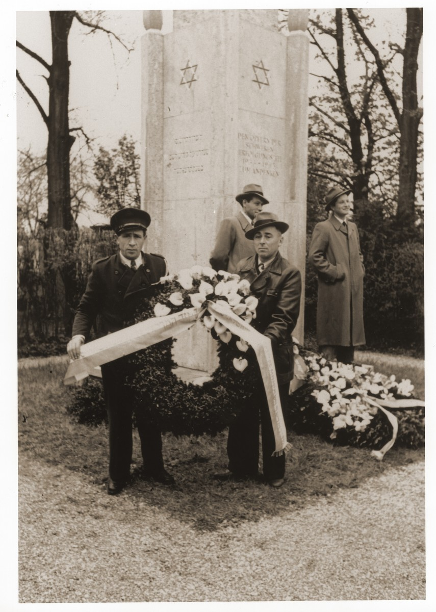Jewish DPs from the Lechfeld displaced persons camp pose with a wreath in front of the memorial to Jewish victims at the Dachau concentration camp.