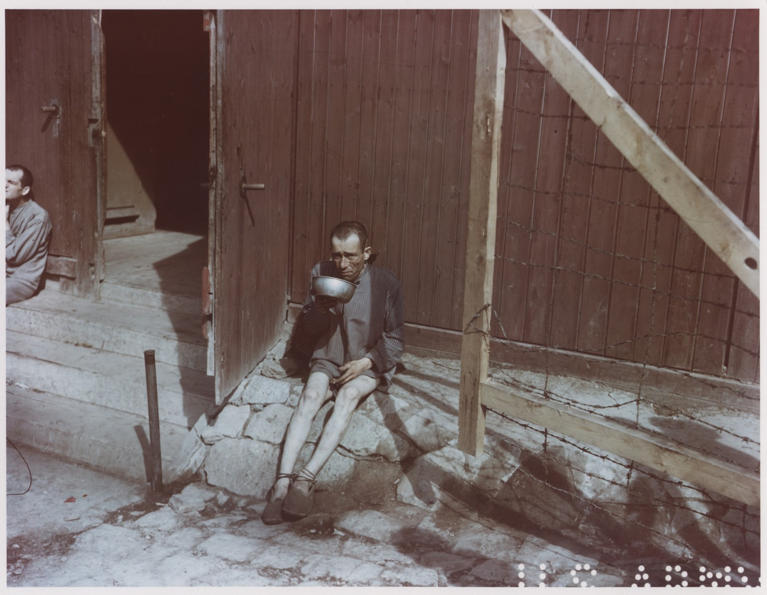 An emaciated survivor drinking from a metal bowl in front of a barracks in Buchenwald.