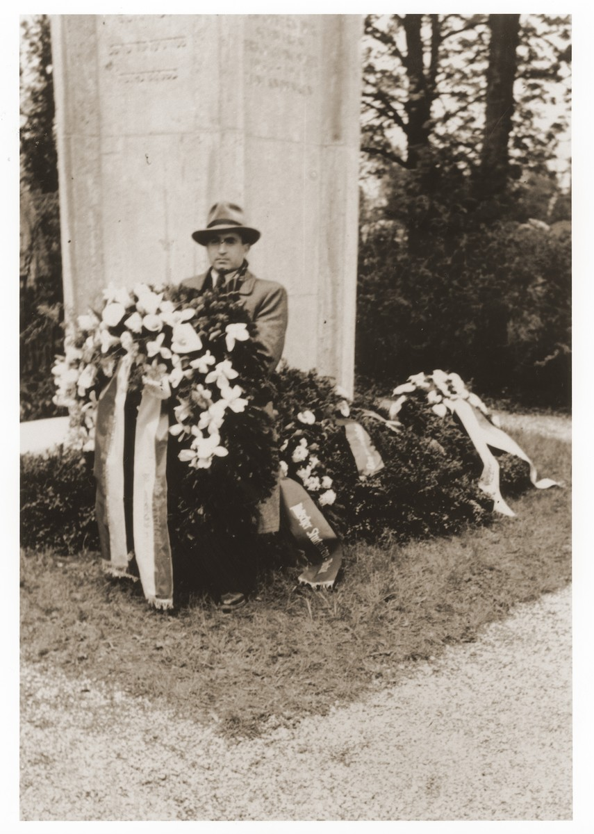 Gerzon Trzcina poses with a wreath in front of the memorial to Jewish victims at the Dachau concentration camp.