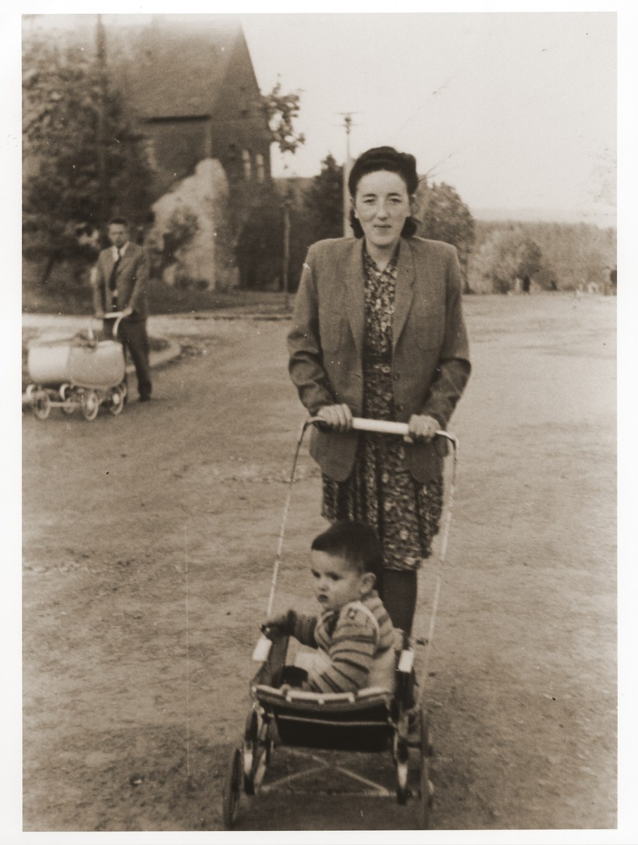 Gittel Trzcina pushes her son Benjamin in a stroller at the Vilseck displaced persons camp.  Gerzon Trzcina was born in Krasnosielc, Poland in 1922.  He was the son of Dina Kassel and Benam Yitzhak, who was a businessman in the leather trade.  Gerzon had one older brother, Jacob, and two sisters, Faiga (b. 1918) and Perl (b. 1920).  When the war broke out, Gerzon was working as a photographer's assistant (among other jobs) in Warsaw.  Following the German invasion of September, 1939, Gerzon was slightly wounded by shrapnel.  Soon after, a drunken German soldier, forcibly cut Gerzon's hair.  When the soldier made him stoop down to pick up the cuttings, Gerzon grabbed the German's gun and ran away.  After a short time in hiding, Gerzon returned to his hometown, where he learned that eighty Jews had been murdered in the synagogue during the first week of the war in one of the first large-scale atrocities against Polish Jews.  Among those killed was Gerzon's eighty-two-year-old grandfather, Haskel Kassel.  Gerzon moved on to Makow Mazowiecki, where he was forced to clean the stables the Germans had set up in the town's synagogue.  In the late fall, Gerzon escaped with his family to Bialystok, where he worked in a tannery until the family was deported to the Soviet interior in June, 1940.  Along with a group of Polish and Jewish refugees, the Trzcinas were sent to the Kiltovo labor camp in northern Russia.  Harsh conditions and poor nutrition led to Gerzon's father's death in the camp.  The family remained in Kiltovo until the German invasion of the Soviet Union in June of 1941.  Soon after, the refugees were allowed to leave the camp, and the Trzcinas moved to nearby Syktyvkar (capital of the Komi republic), where Gerzon worked in a construction company and later in a tannery.  In Syktyvkar, Gerzon was reunited with Gittel Blankitner, a Jewish refugee from Mlawa, whom he had met earlier in his travels in the Soviet Union.  (Gittel's father perished in Aushwitz, and her 