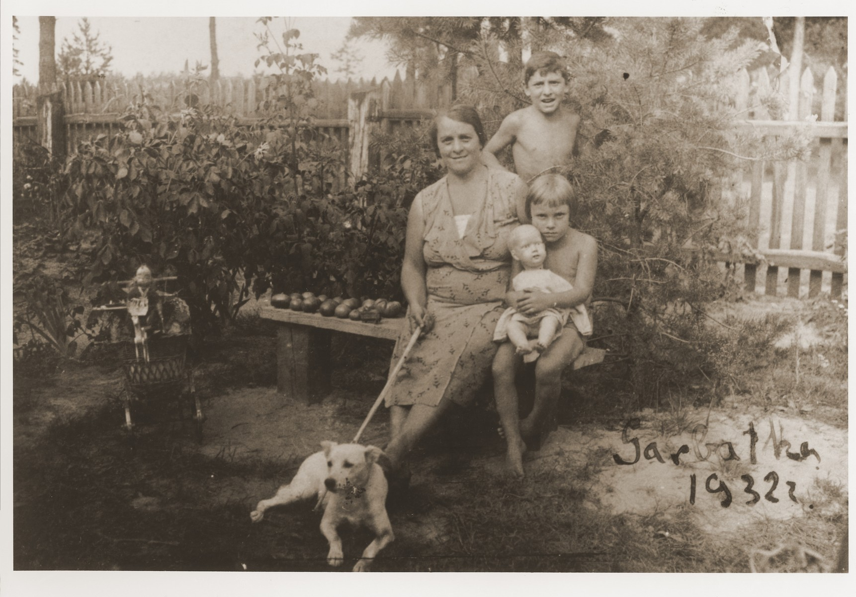 Ester Fiszman poses with her children, Julek and Saba, in the yard of their summer home.